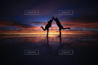 背景の夕日とビーチを歩いて男の写真・画像素材[928051]