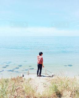 水の体の横に立っている人の写真・画像素材[1401110]