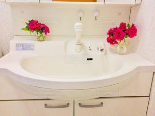テーブルの上の花の花瓶付きのバスルーム - No.789894