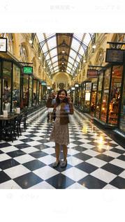 鉄道駅の隣に立っている女性の写真・画像素材[790322]