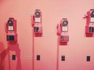 壁に並ぶピンクのレトロ電話 - No.797739