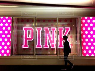 店の窓の前に立っている男の写真・画像素材[842333]