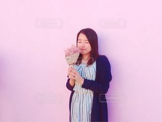 ピンクの壁の前で女性と花束の写真・画像素材[842378]