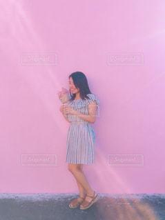 ピンクの壁と花束を持つ女性の写真・画像素材[842938]