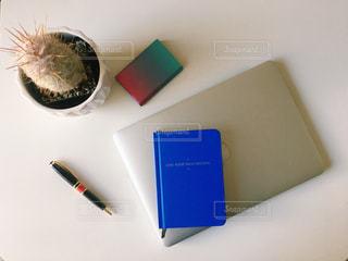 机の上のパソコンとノートの写真・画像素材[920390]