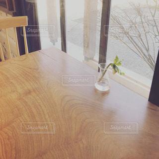 木製のテーブルの上に座っている花の花瓶の写真・画像素材[2140665]