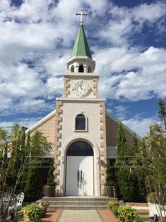 建物の側に時計と大きな背の高い塔の写真・画像素材[803604]