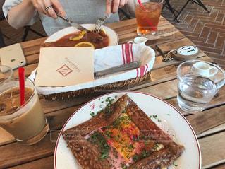 食品のプレートをテーブルに座っている女性の写真・画像素材[803612]