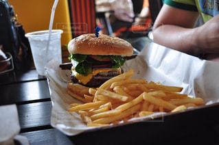 皿にサンドイッチとポテトのテーブルに座って人の写真・画像素材[805584]