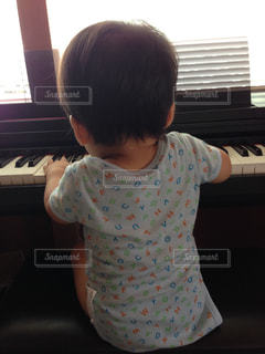 ピアノの前に座っている赤ちゃんの写真・画像素材[807041]