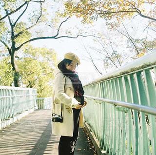 フェンスの近くの歩道に立っている人の写真・画像素材[894405]