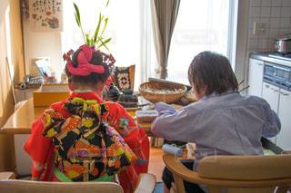 窓の前のテーブルに座っている少年の写真・画像素材[820621]