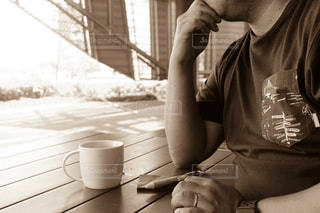 携帯電話を使用してテーブルに座っている男の人 - No.823723