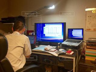 コンピューターの前で机に座っている男の写真・画像素材[922084]