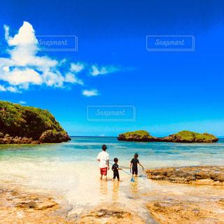 水の体の近くのビーチの人々 のグループの写真・画像素材[899473]