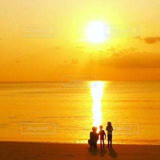 背景の夕日とビーチの上を歩く人々 のグループの写真・画像素材[975897]