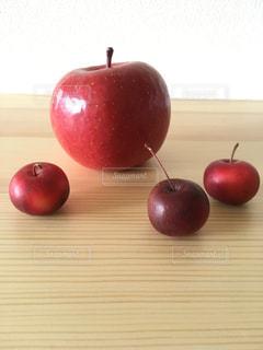 テーブルの上に座っている赤いリンゴの写真・画像素材[3172389]