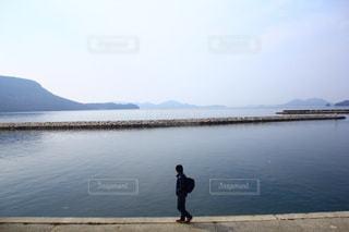 水の体の横に立っている人の写真・画像素材[920677]