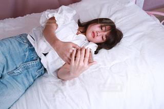 ベッドの上で横になっている人の写真・画像素材[1064347]