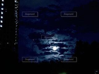夜の高層ビルと明るい月の写真・画像素材[3718446]