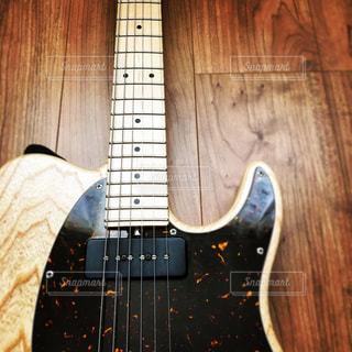 木の表面に黒いギターの写真・画像素材[820937]