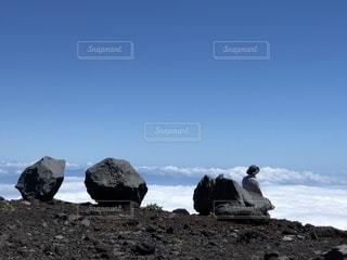 岩が多い丘の上に立っている人の写真・画像素材[1408778]