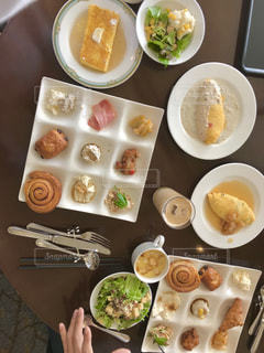 テーブルの上の皿の上に食べ物のトレイの写真・画像素材[1084330]