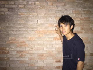 レンガ壁の前に立っている男の写真・画像素材[1694452]