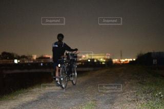 未舗装の道路を自転車に乗る男の写真・画像素材[1727298]