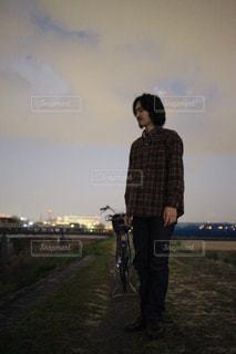 曇り空の前に立っている男の写真・画像素材[1727330]