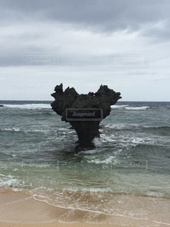 海の横にあるビーチの上を歩く男の写真・画像素材[904080]