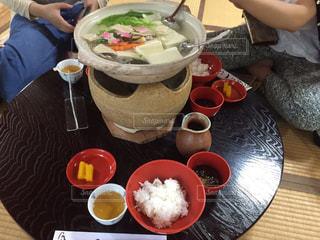 食品のプレートをテーブルに座っている女性の写真・画像素材[1697200]