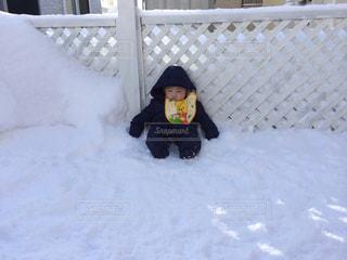 雪の中で座っている小さな男の子の写真・画像素材[867025]