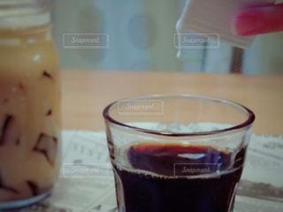近くのテーブルの上のガラスのコップで飲み物を - No.932722