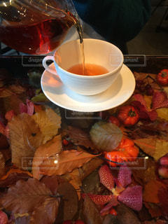 コーヒー カップの横に座っているぬいぐるみの山の写真・画像素材[942785]