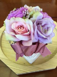 木製テーブルの上のピンクの花の写真・画像素材[955081]