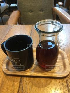一杯のコーヒーと木製のテーブルの上のビールのグラス - No.985876