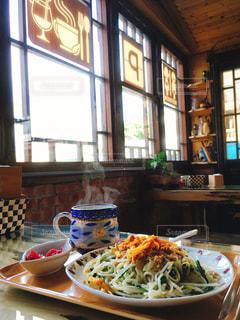 ウィンドウの横のテーブルの上に食べ物のプレートの写真・画像素材[872905]