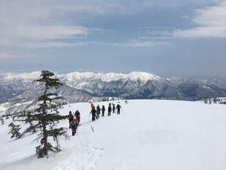 雪の山でスキーに乗っている人のグループ - No.944542