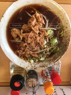 木製テーブルの上に座っているスープのボウルの写真・画像素材[1220612]