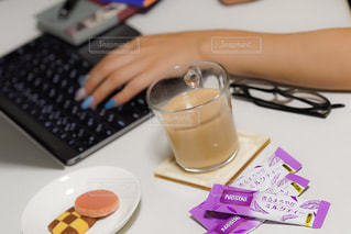 ラップトップを使用してテーブルに座っている人の写真・画像素材[1292970]