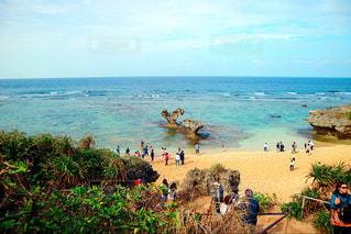 水の体の近くのビーチの人々 のグループの写真・画像素材[1044505]