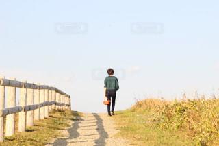 未舗装の道路を歩いて男 - No.878367