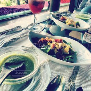 食品のプレートをテーブルに座っている女性の写真・画像素材[1145174]