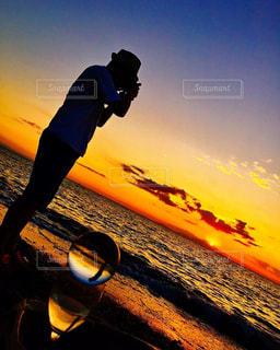 バック グラウンドで夕日を持つ男の写真・画像素材[1249868]