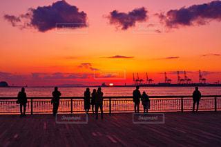 背景の夕日と桟橋を歩いている人のグループの写真・画像素材[1269098]