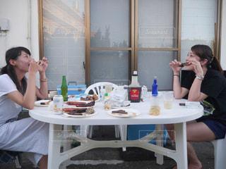 食事のテーブルに座っている女性の写真・画像素材[1245604]