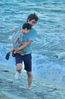 波打ち際でビックリする親子の写真・画像素材[1447779]