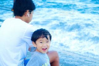 水の体の横に立っている少年の写真・画像素材[1590869]