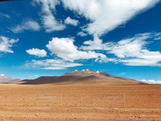 近くに砂漠のフィールドと背景の山のアップの写真・画像素材[1105443]
